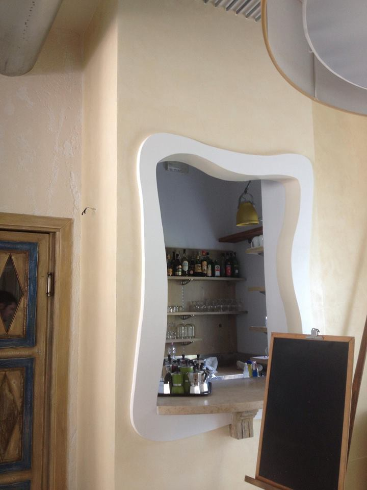 una finestra con vista di bottiglie e bicchieri su delle mensole e una lavagna