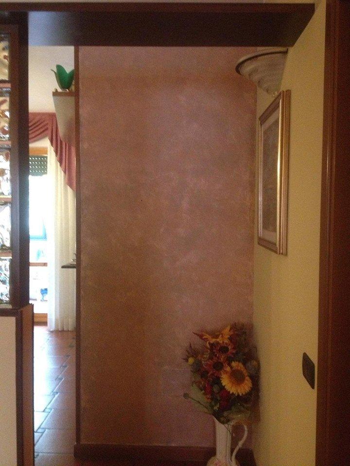 un muro di colore rosso e grigio sfumati, un vaso di fiori e una parete gialla