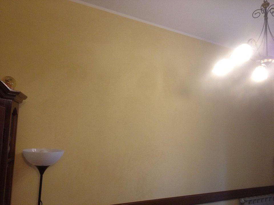 una lampada da terra e una parete gialla con finiture marroni