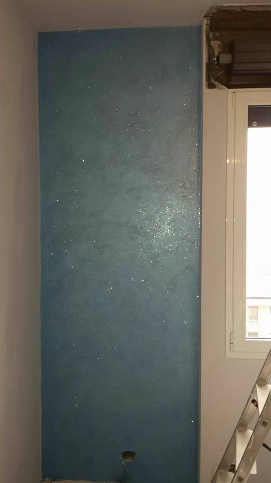 Vista parziale di una finestra, una scala e una parete dipinta di blu verdastro