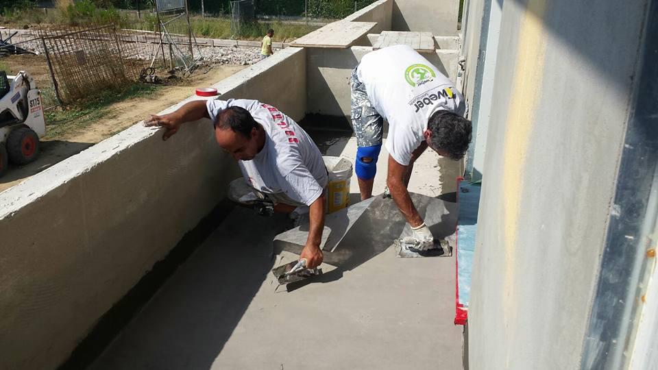 Due operai spianando il cemento con la piana