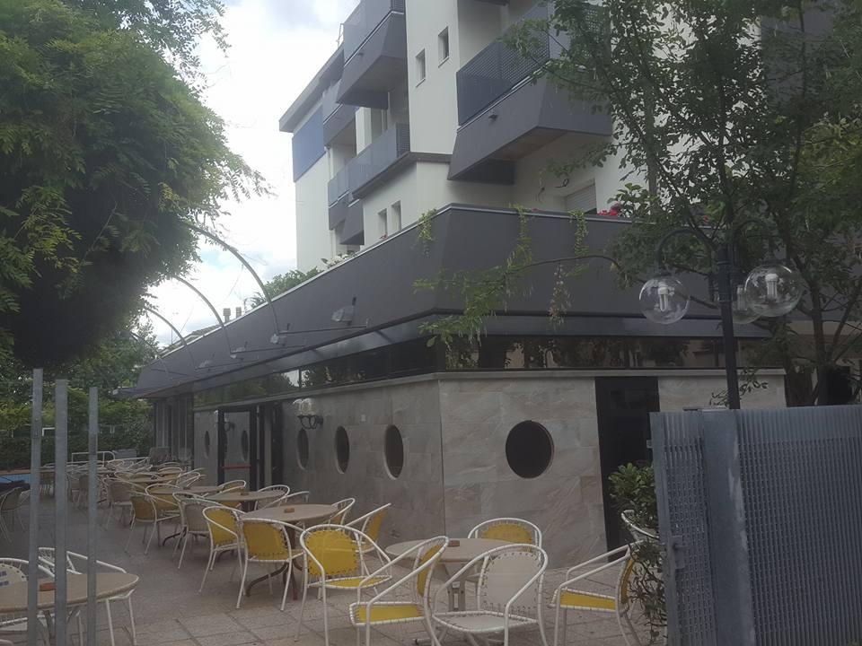 Vista della terrazza , tavole rotonde e sedie creme e gialle