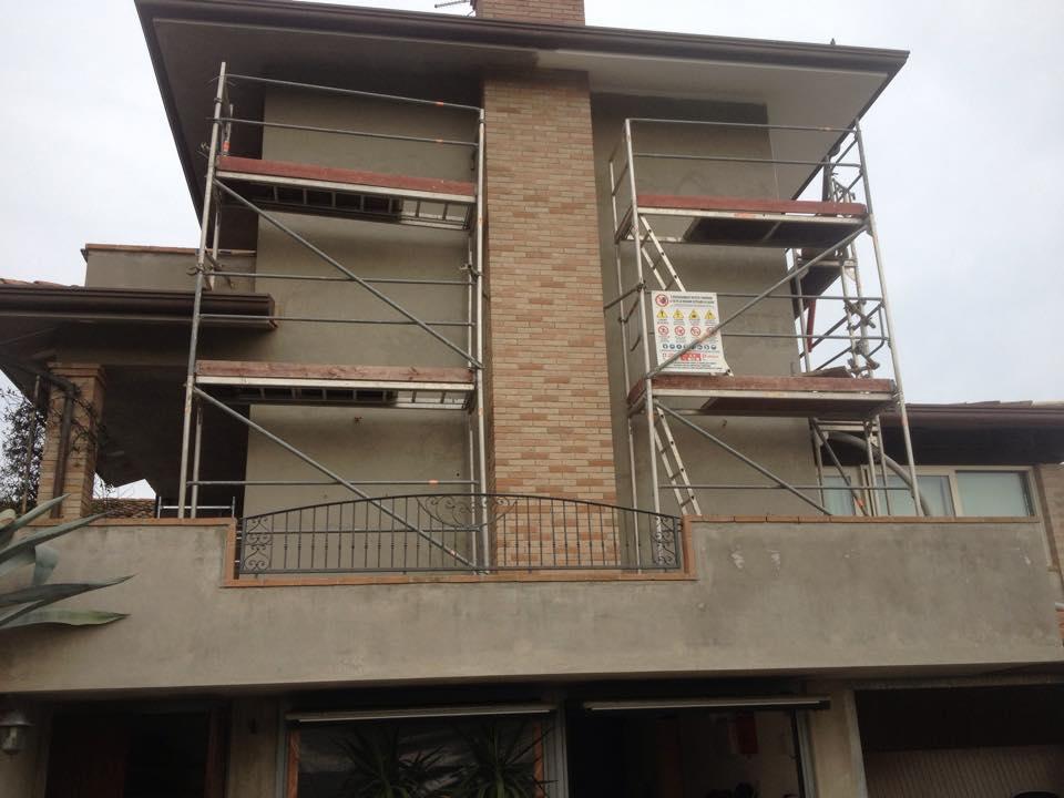 Esteriore di una casa con ponteggi nella terrazza coprendo la parete