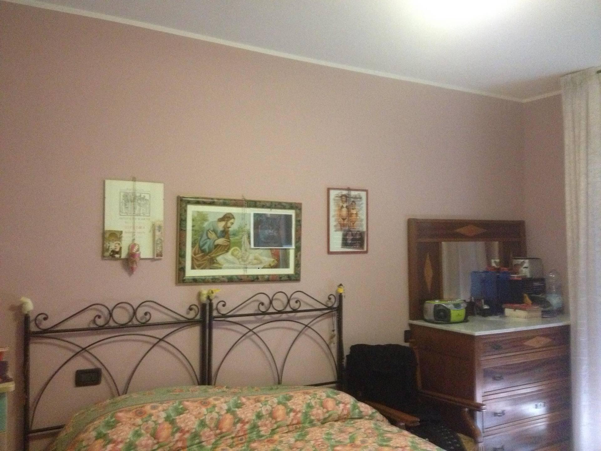 Vista di una stanza dipinta di colore rosa e con tabelle religiosi nelle pareti