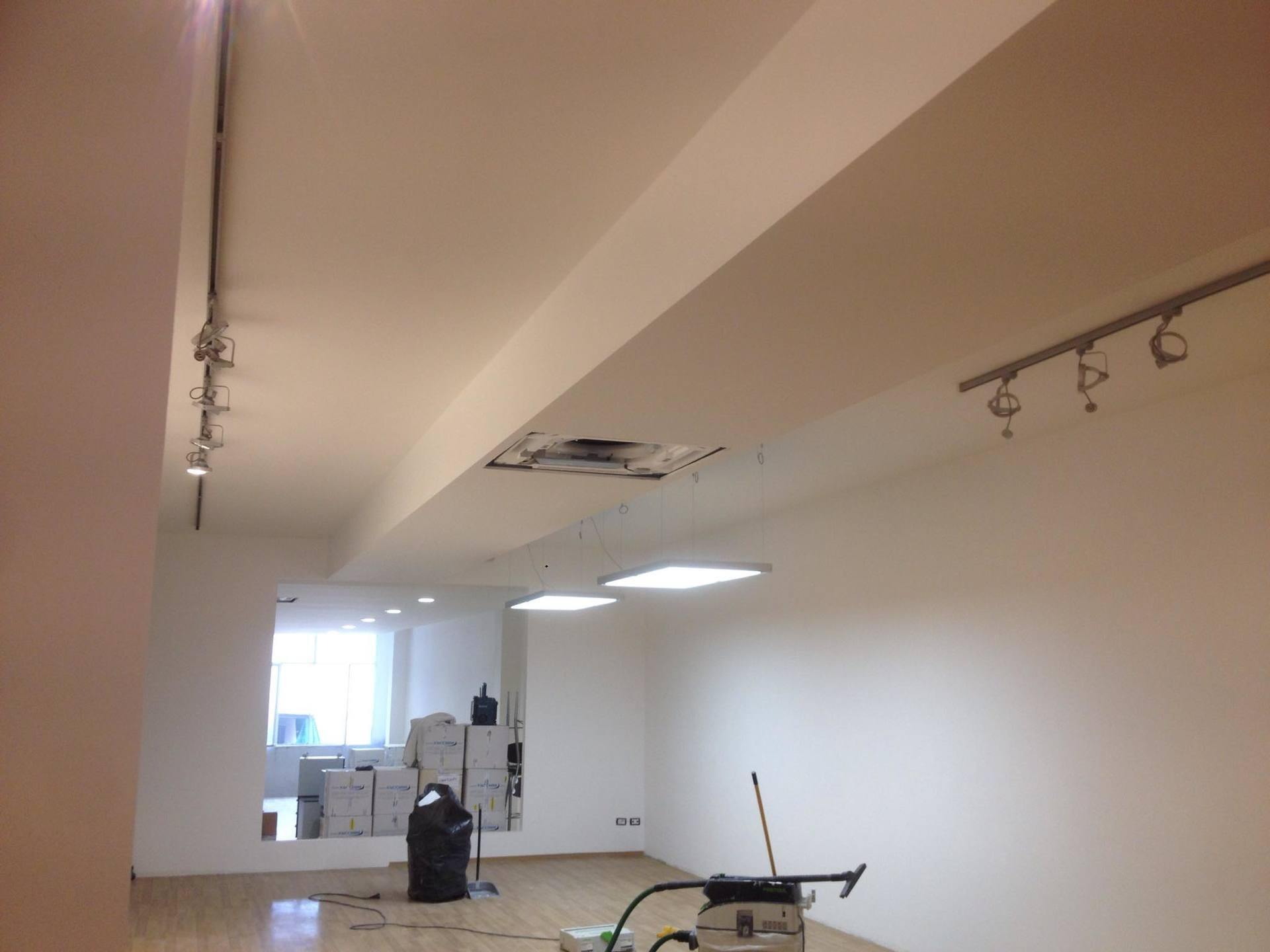 Locale con pavimento in legno,l buco nel tetto per successiva nuova sistemazione,guia elenco per installare le lampade ,un aspiratore e casse di cartone