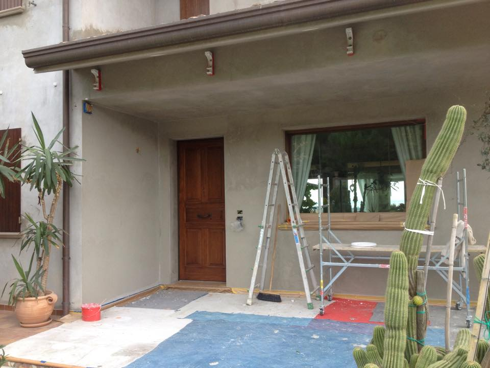 Entrata di una casa, scale, un piccolo ponteggio e il suolo protetto con teloni