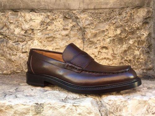 una forma di scarpa a legno, un centimetro e una scarpa di pelle