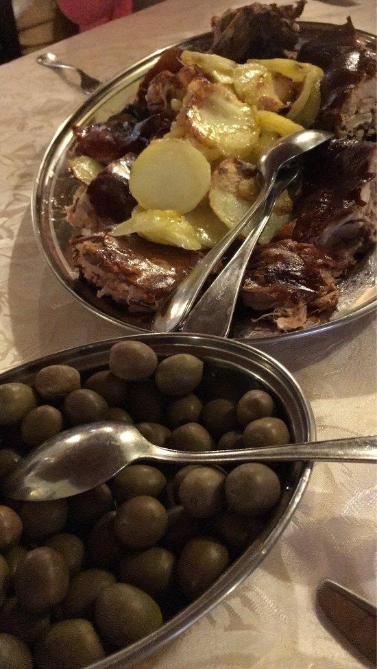 un vassoio di carne con patate e una ciotola di olive verdi