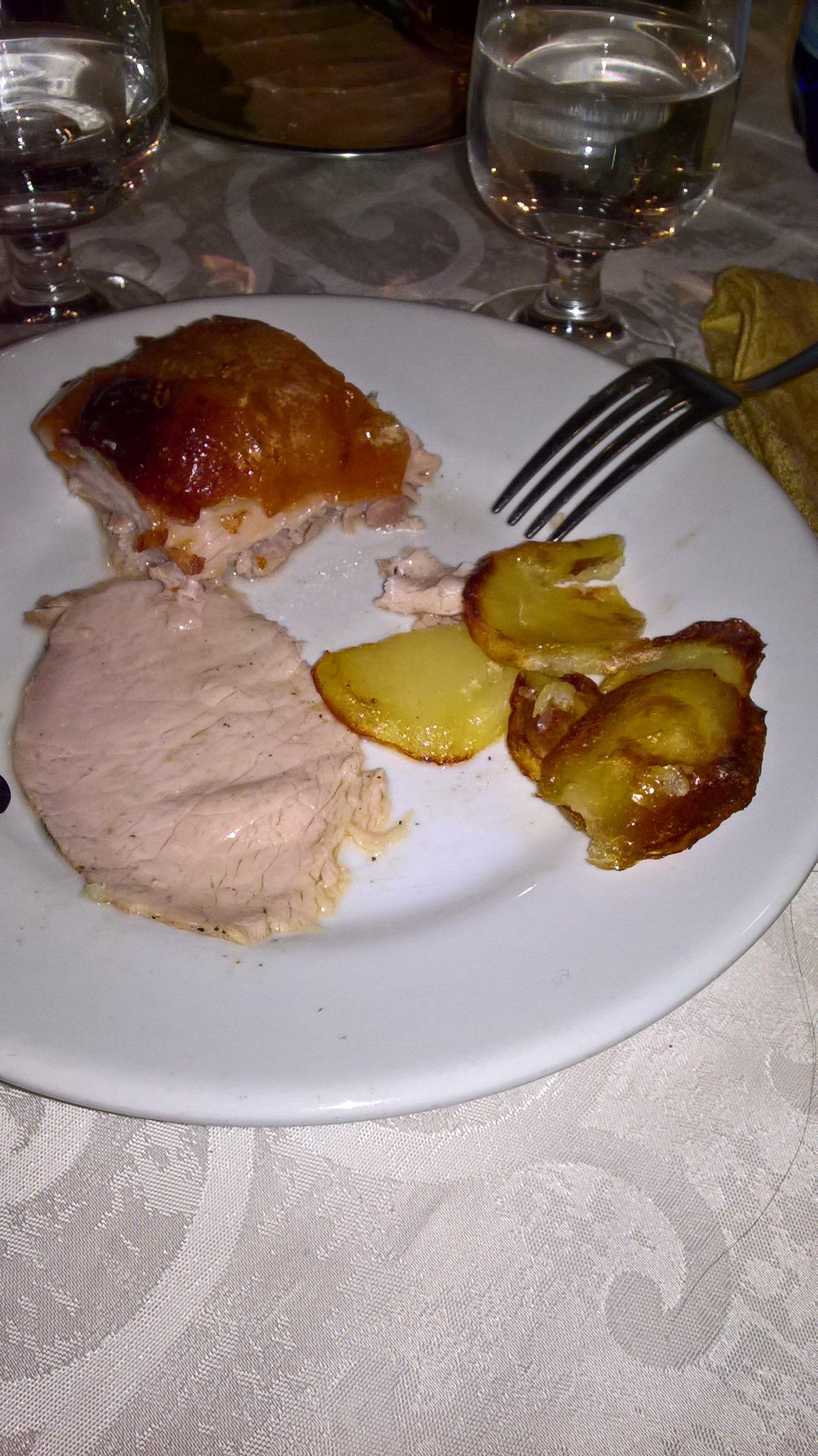 un piatto a base di carne e delle patate accanto
