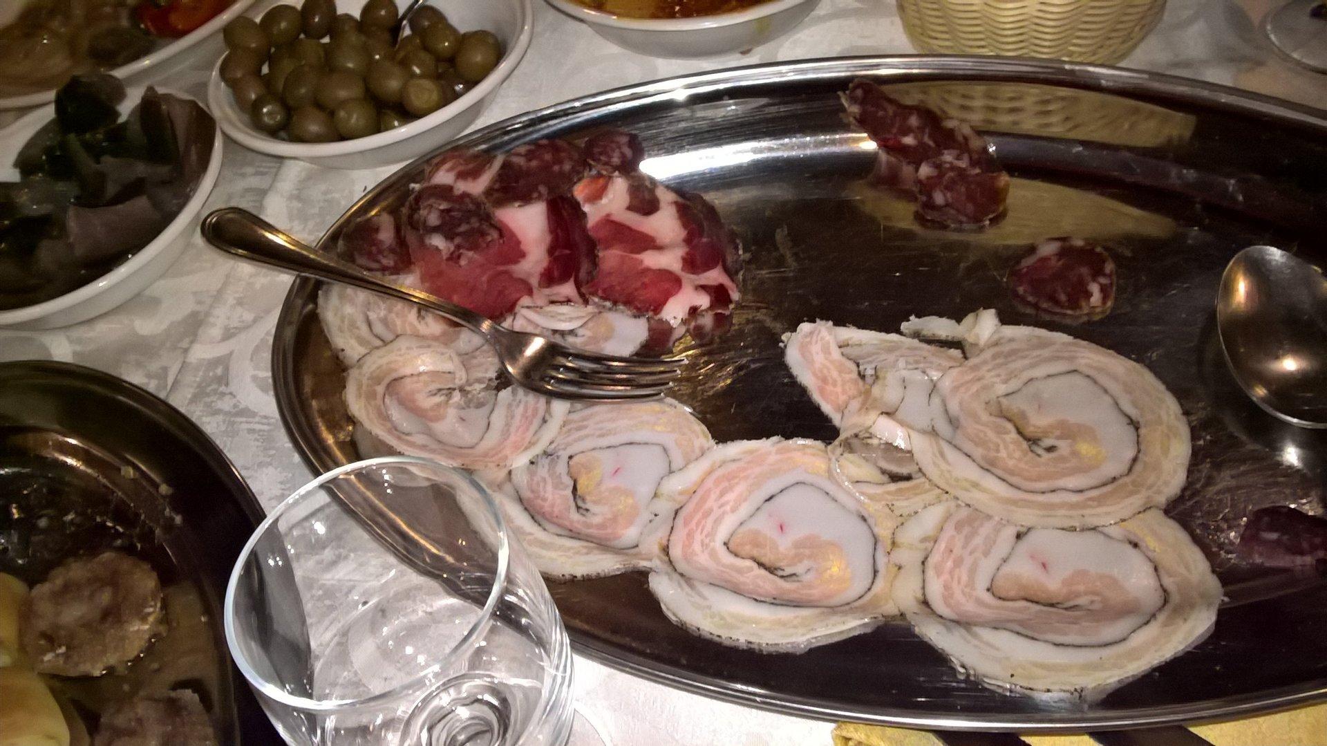 un vassoio con dei salumi e accanto una ciotola di olive