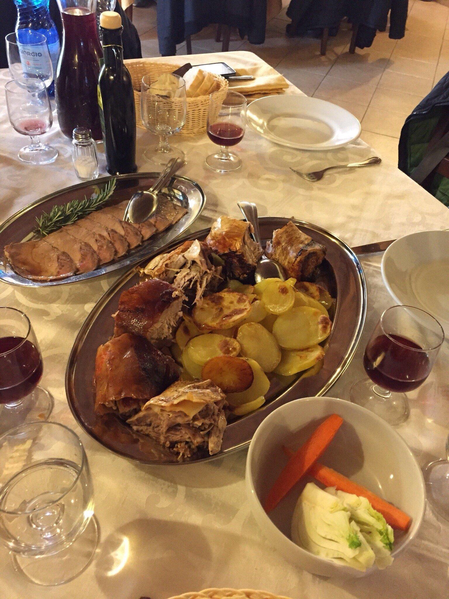 un tavolo con un vassoio con arrosto di carne e delle patate