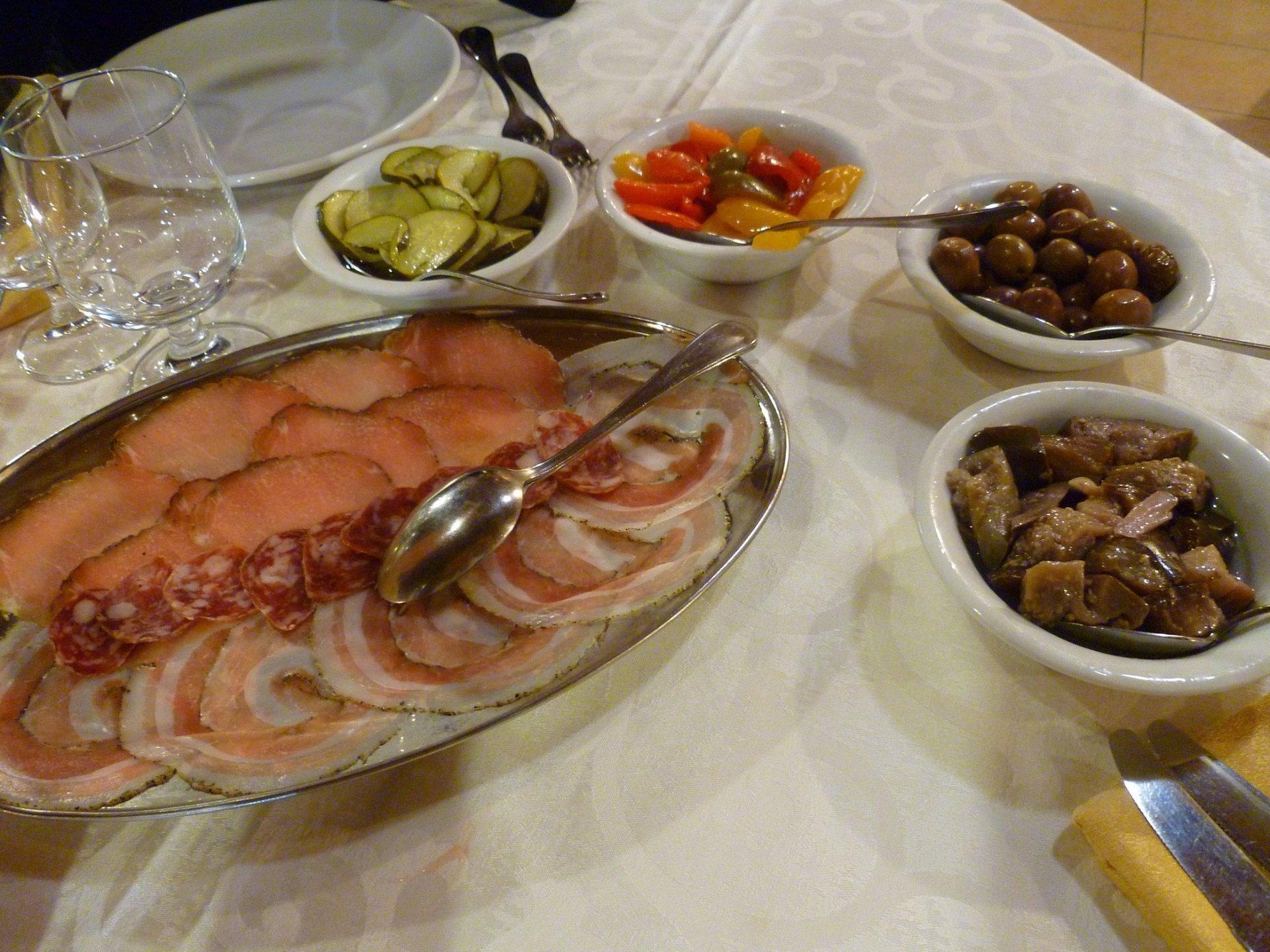 un vassoio di salumi, delle ciotole con zucchine, peperoni e olive