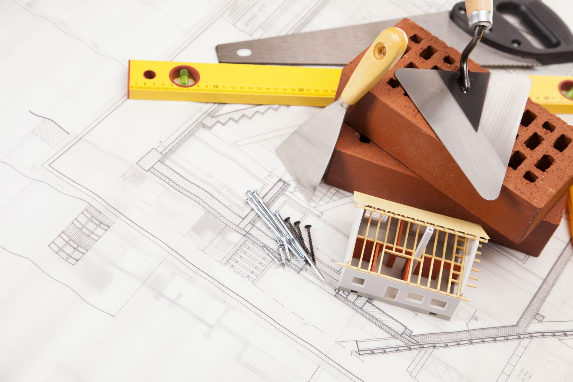 un disegno di un progetto edile,una spatola,VITI,mattoni,sega e raschietto