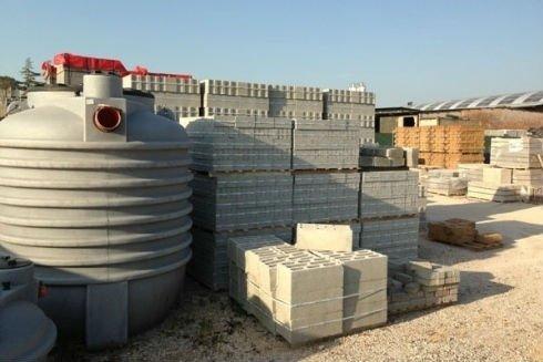 dei blocchi di cemento su dei bancali e una grossa tanica