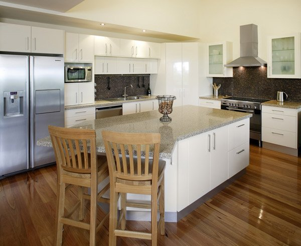 kitchen after renovation with white cupboards and granite countertops