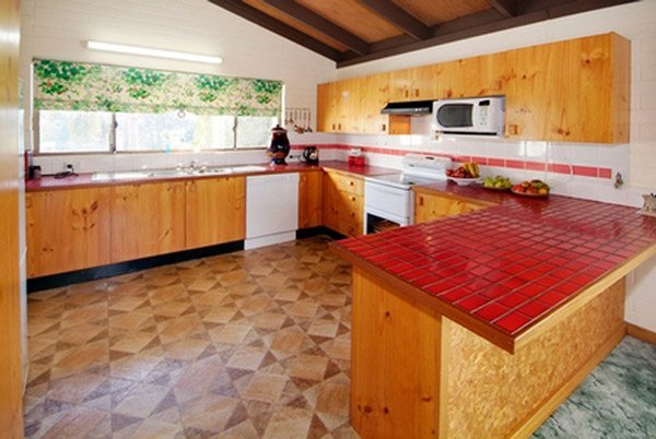 dated kitchen with wood cupboards and linoleum floor