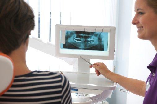 vista dello studio dentistico con le apparecchiature un lettino arancione e un monitor dove viene visualizzata una lastra