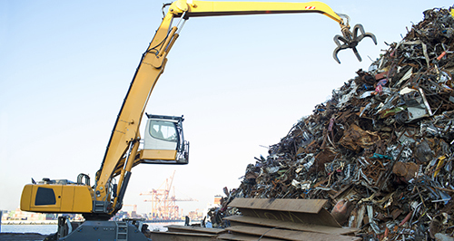 Excavator picking scrap metal for recycling in Burlington, WV