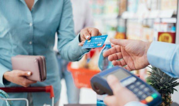 signora che paga con una carta di credito
