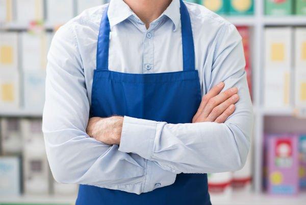 addetto del supermercato con grembiule blu