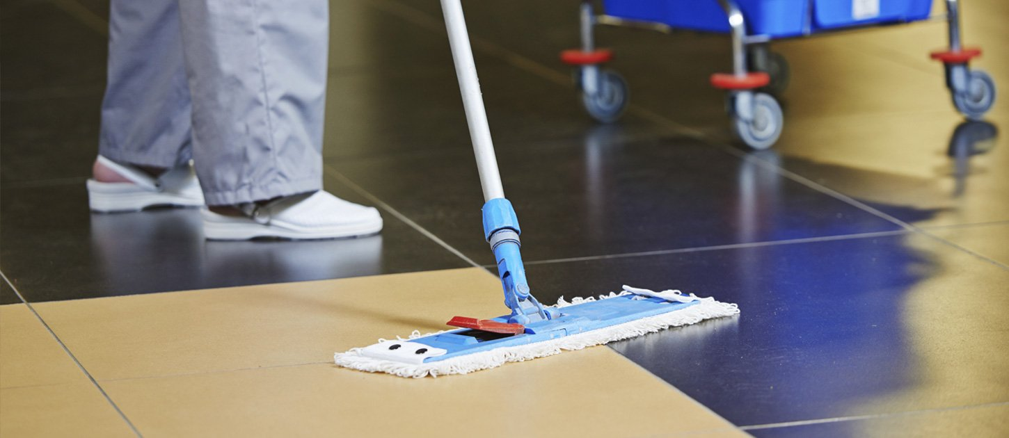 cleaner polishing a floor with a brush