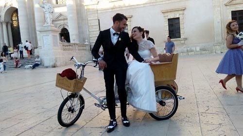 Una coppia di sposi in bicicletta