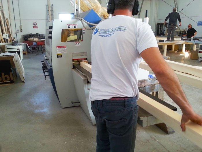 uomo che tagli assi di legno