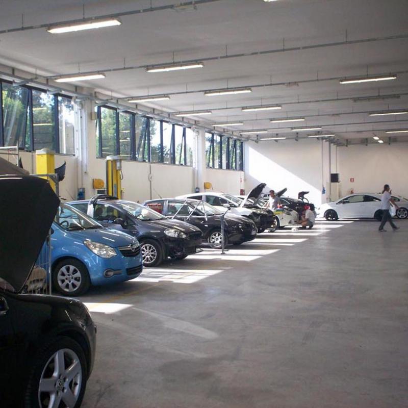 vista laterale fila di macchine durante riparazione in una officina auto