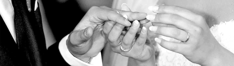 Foto di due mani durante lo scambio di fedi