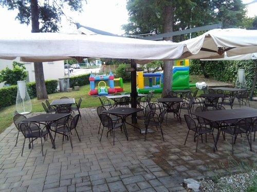 zona esterna di ristorante con sedie e tavoli