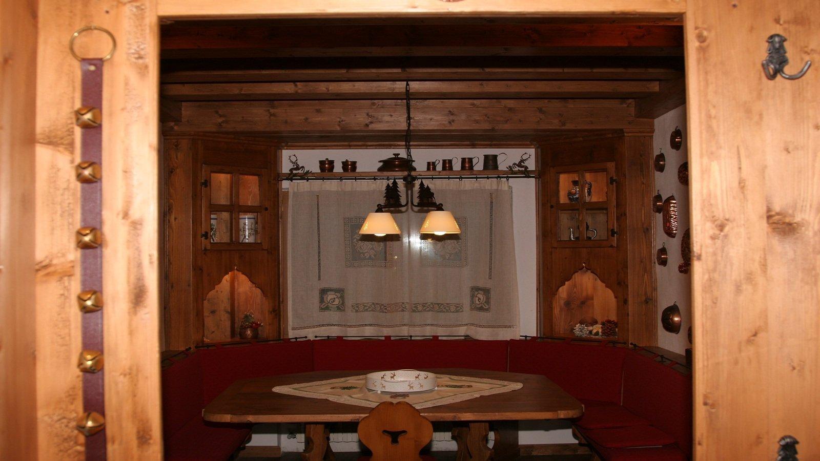 una stanza in legno con un tavolo una panca e delle luci a sospensione