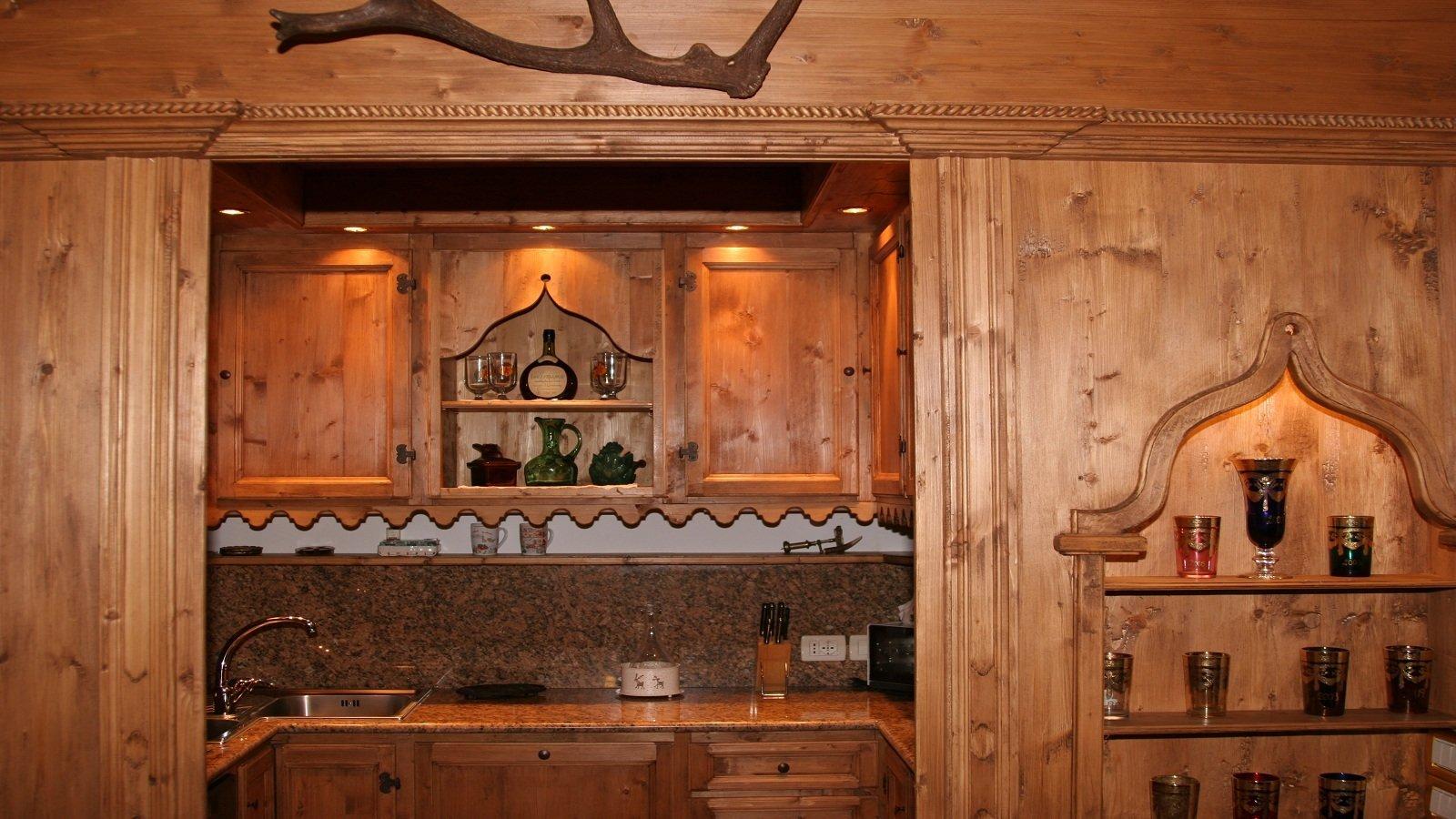 una cucina in legno e delle mensole con dei bicchieri