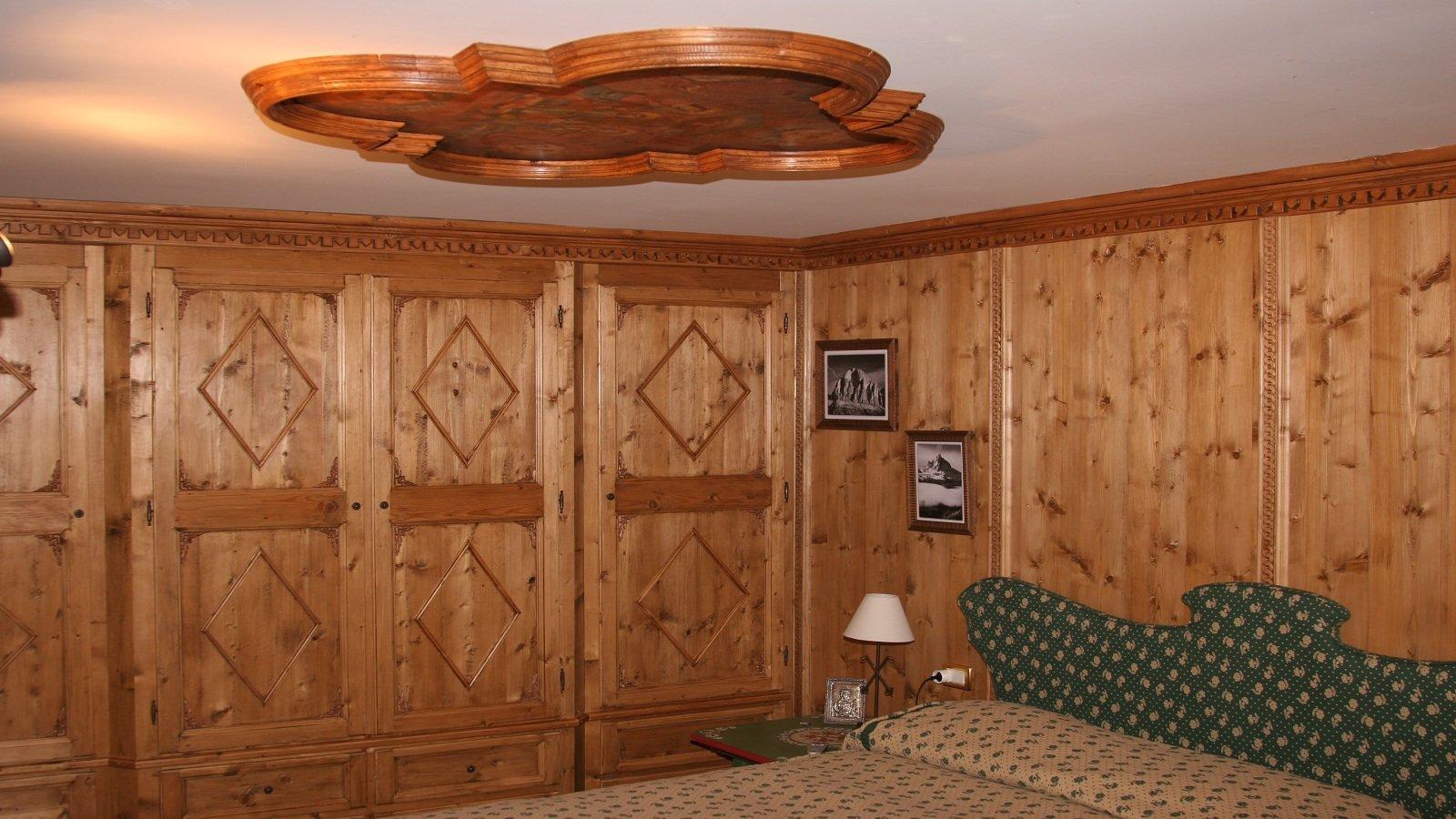 una camera da letto con armadi in legno e due quadretti