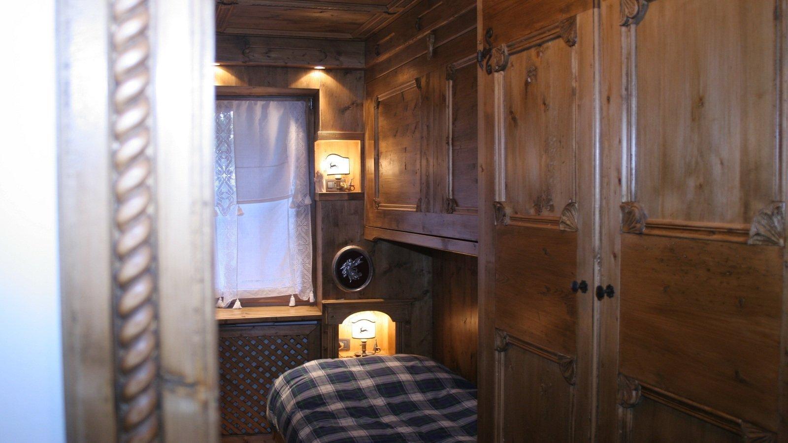 una cameretta con dei mobili in legno e un letto singolo