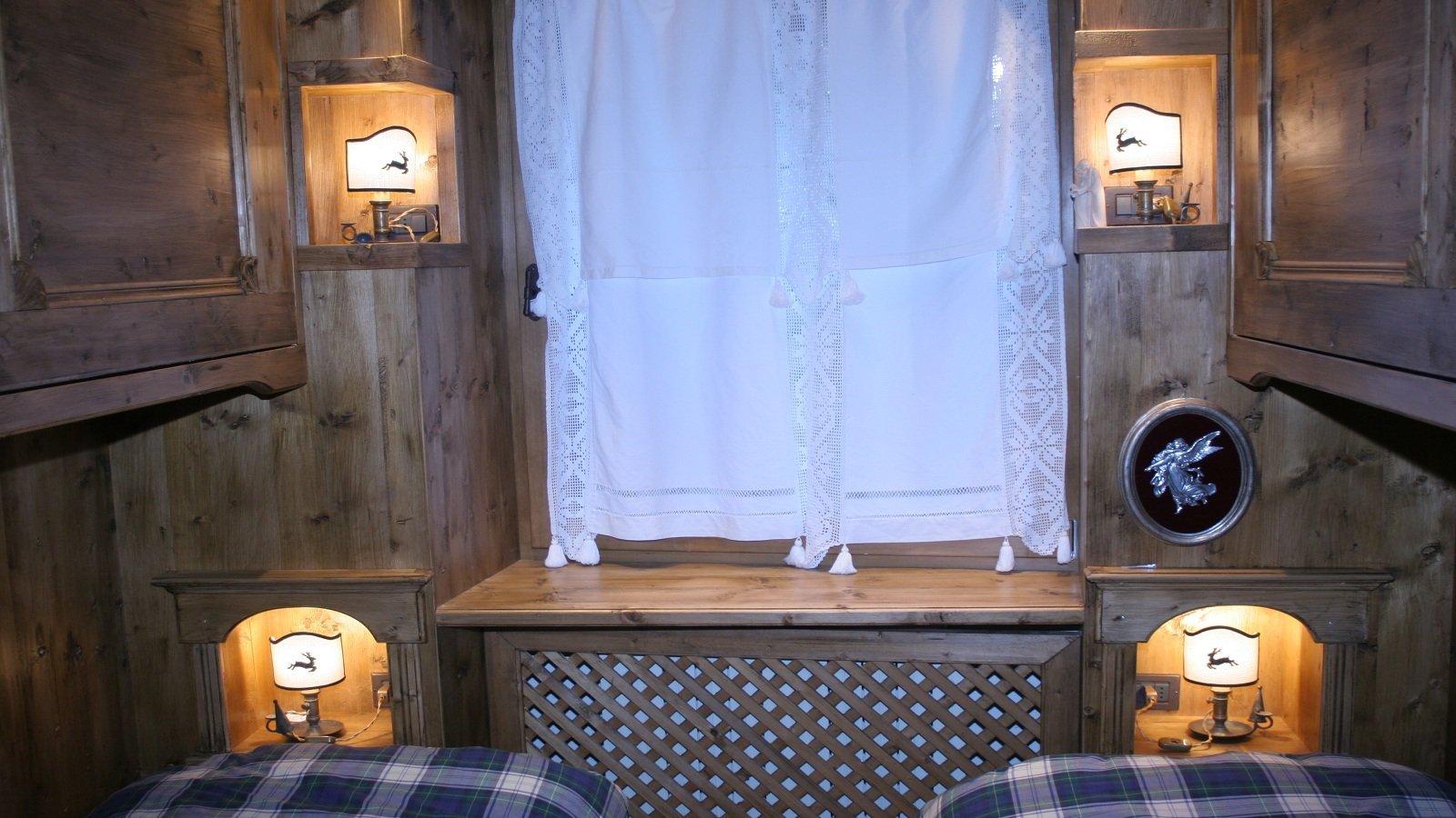 due letti, una finestra e un calorifero coperto da una griglia in legno
