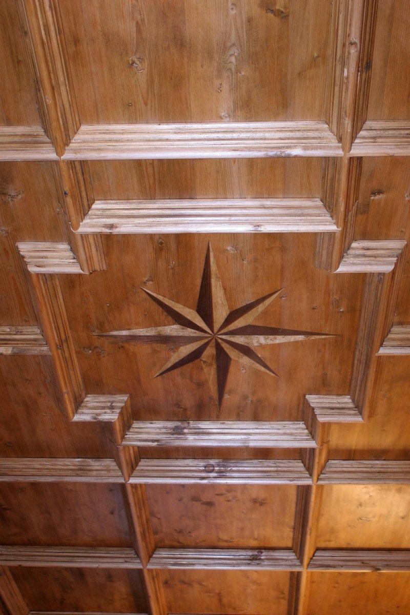 una lavorazione in legno con il disegno della rosa dei venti