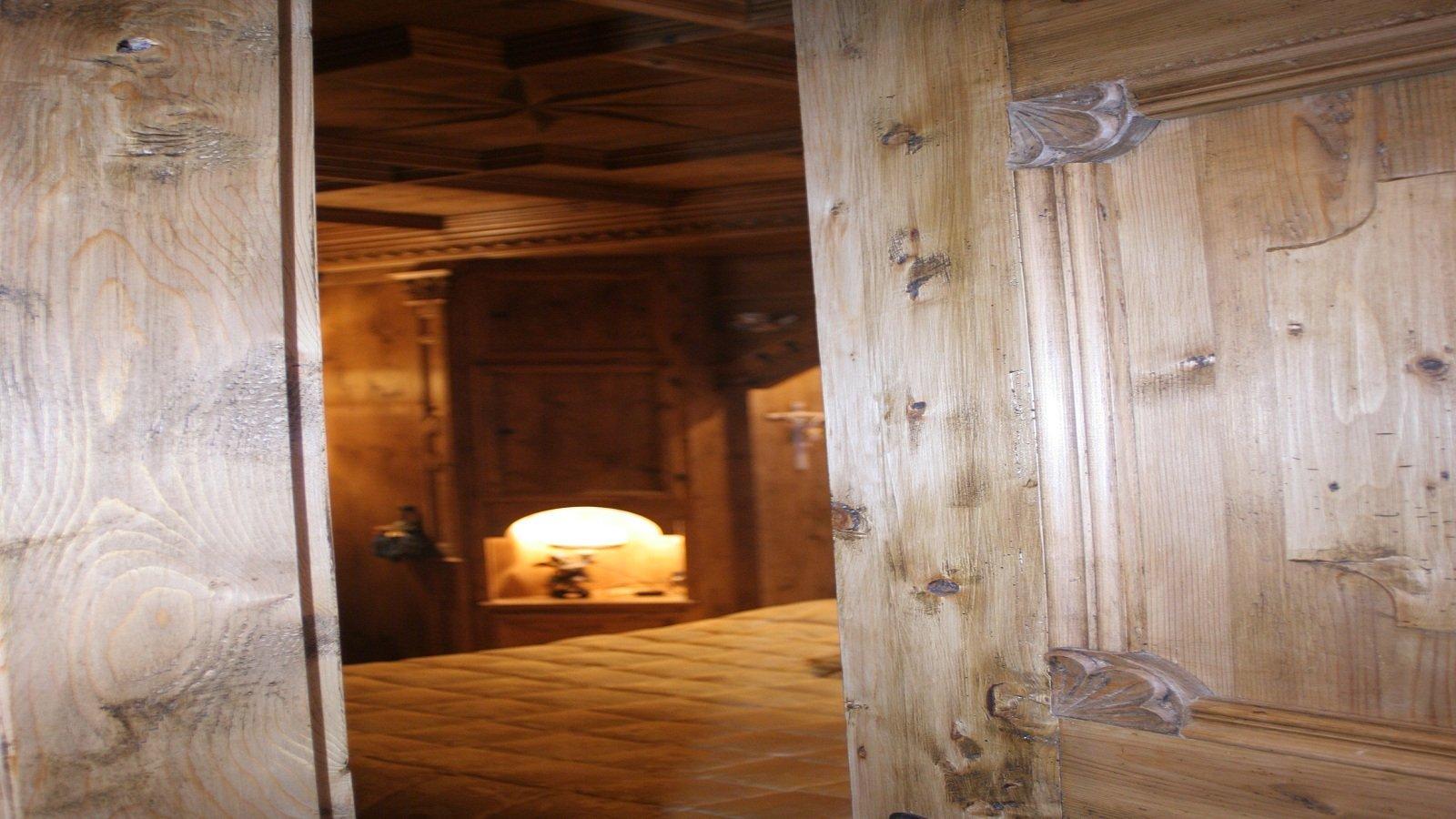 una porta socchiusa e l'interno di una camera da letto in legno