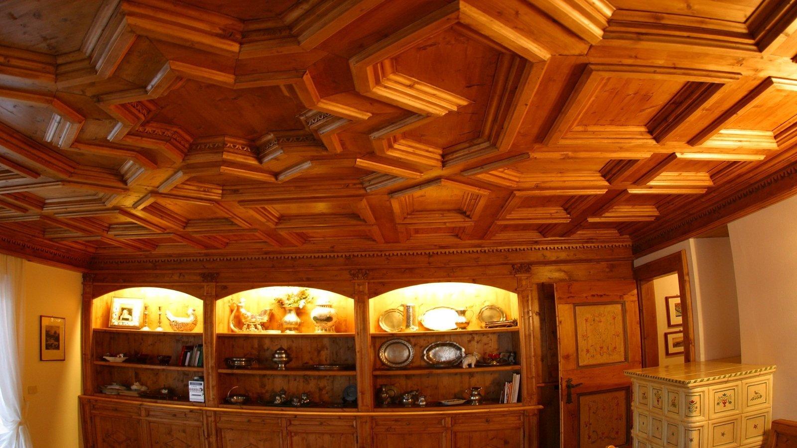 una stanza con mobili e soffitto in legno e delle mensole con piatti in ferro e altri oggetti