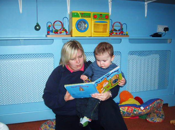 boy reading book in day care