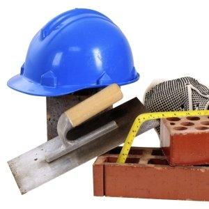 utensili e materiali da lavoro come casco, spatola, metro, mattoni forati