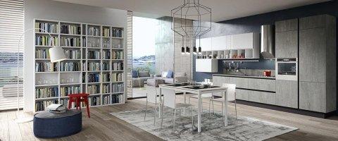 zona giorno con cucina, tavolo, poltrona e libreria