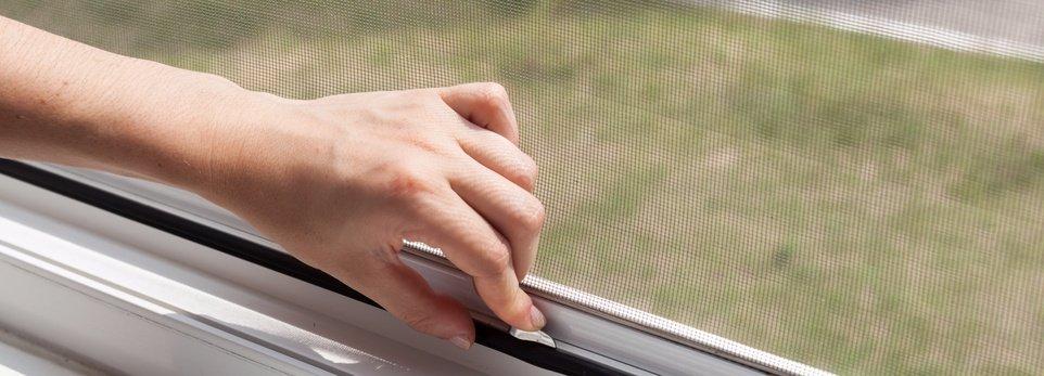 una mano che chiude una zanzariera