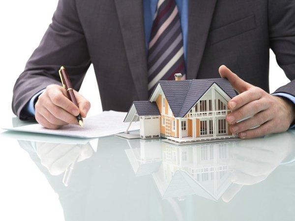 Persona in giacca e cravatta che scrive con un modellino di una casa