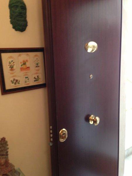 una porta in legno scuro con dei pomelli dorati