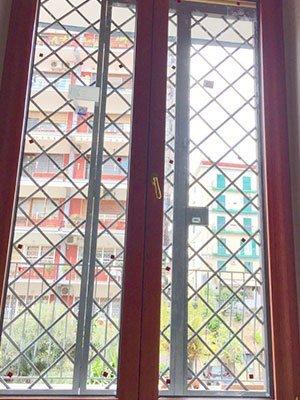 una porta finestra in legno con delle griglie