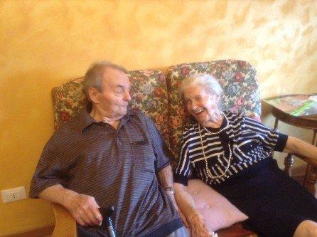 Anziana che regge la mano all'ospite della residenza per anziani