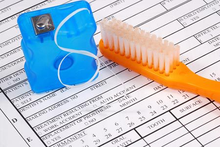Close up to patient form and floss and toothbrush