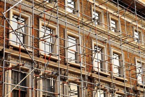 Faccia di un palazzo coperta dall'impalcatura di un'impresa edile