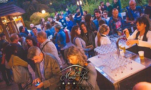 Persone durante un evento fuori dal ristorante e camerieri che servono birra alla spina