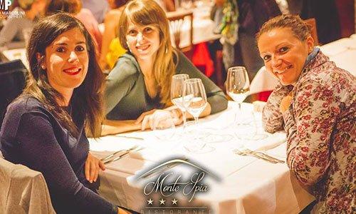 Tre donne al tavolo, sorridenti con tre bicchieri di vino